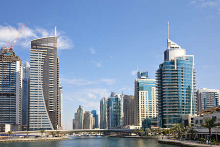 DUBAI, UNITED ARAB EMIRATES - NOVEMBER 23, 2019: Dubai Marina skyscrapers and canal with palm trees and people in a sunny day, blue sky in Dubai Sajtókép
