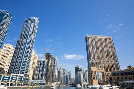 DUBAI, UNITED ARAB EMIRATES - NOVEMBER 23, 2019: Dubai Marina skyscrapers and canal with yachts in a sunny day, blue sky in Dubai