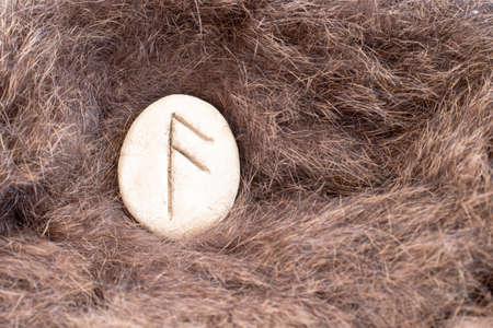Ansuz Nordic stone rune on fur. Letter Aesc of the Viking alphabet. Stock Photo
