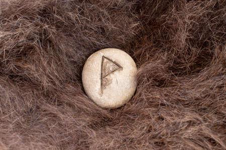 Wunjo Nordic stone rune on fur. Letter Wyn of the Viking alphabet. Stock Photo