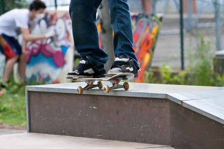 Skater Grinding 50 50 on wall in Skate park with graffiti painter behind