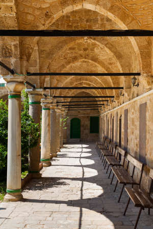 Columned portico with Stone Pillars and  wooden Benches in Mosque in Acri Akko Israel Editorial