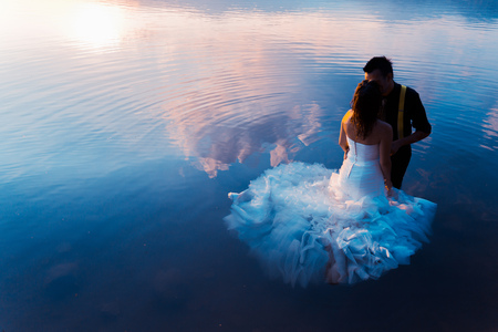 bride and groom on the water in the lake at sunseet, trash the dress