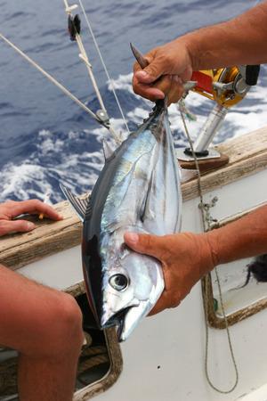 Man fishing tuna from boat at sea photo