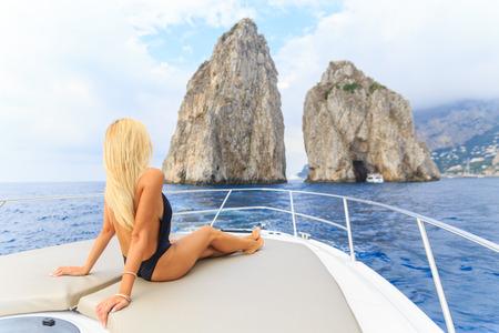 Junge sexy Frau liegt im weißen Kleid genießen Wolken am Himmel auf Yacht auf dem Meer in der Nähe von Faraglioni Insel Capri Italien Standard-Bild - 36522377