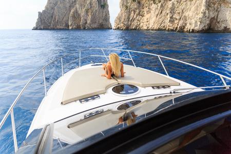 Junge sexy Frau liegt im weißen Kleid genießen Wolken am Himmel auf Yacht auf dem Meer in der Nähe von Faraglioni Insel Capri Italien Standard-Bild - 36522514