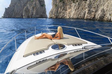 Junge sexy Frau liegt im weißen Kleid genießen Wolken am Himmel auf Yacht auf dem Meer in der Nähe von Faraglioni Insel Capri Italien Standard-Bild - 36522516