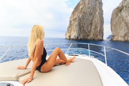 Junge sexy Frau liegt im weißen Kleid genießen Wolken am Himmel auf Yacht auf dem Meer in der Nähe von Faraglioni Insel Capri Italien Standard-Bild - 36522500