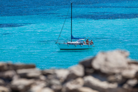 Yatch in ein blaues Meer hinter den Felsen Standard-Bild - 36522511