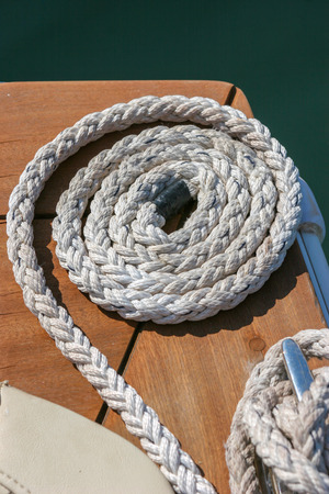 Close-up of a mooring rope tied around a cleat on a wooden pier - Nautical mooring rope