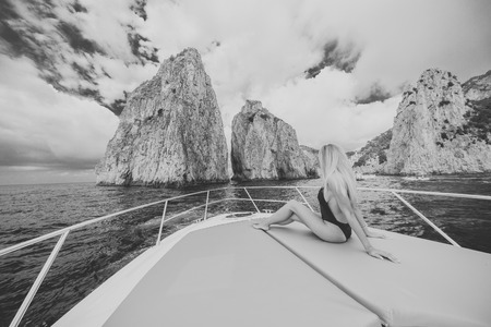 tans: Young sexy woman lies in white dress enjoying clouds in the sky on yacht at the sea near faraglioni island capri italy