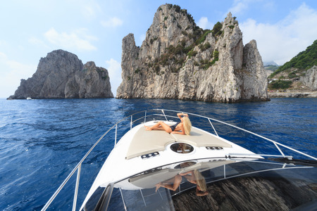 Young sexy woman lies in white dress enjoying clouds in the sky on yacht at the sea near faraglioni island capri italy