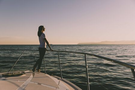 happy woman on the yacht, on the prow of luxury yacht