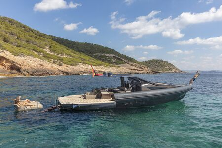 people in relax on the inflatable motor boat in formentera, navigate in the beautiful sea of baleares islands