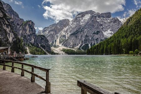 Braies Lake in Dolomites mountains forest trail in background, Sudtirol, Italy. Lake Braies is also known as Lago di Braies. The lake is surrounded by forest which are famous for scenic hiking trails.