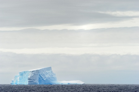 calving: Iceberg floating in ocean Stock Photo