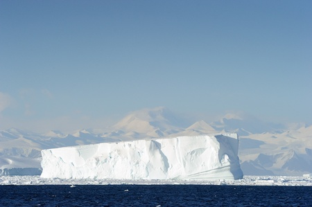 calving: Iceberg in front of coast Antarctica. Stock Photo
