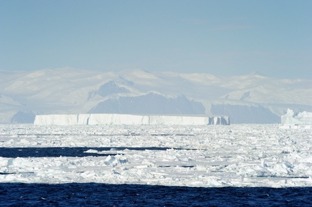 calving: Iceberg and pack-ice in front of coast Antarctica.