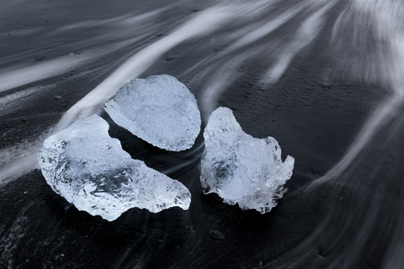 Ice block on a beach with lava stones and water floating over  photo