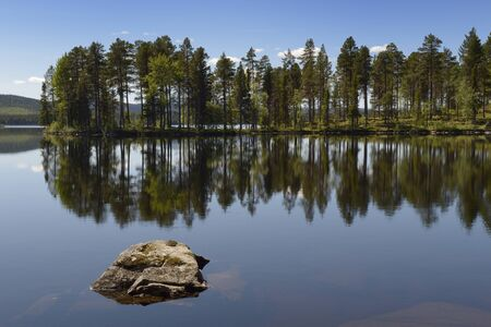 serenety: Swedish lake with reflection and rock in foreground.