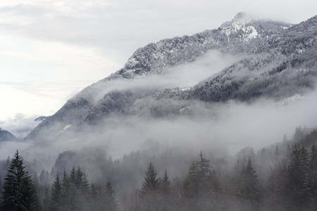 archetypal: Mountain valley with snow and low clouds.