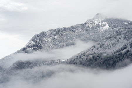 western european: Mountain valley with snow and low clouds.