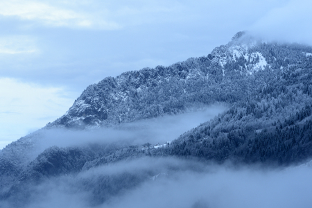 prototypical: Mountain valley with snow and low clouds.