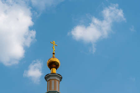 Golden dome and cross of Church on blue sky background with cirrus clouds with copy space.