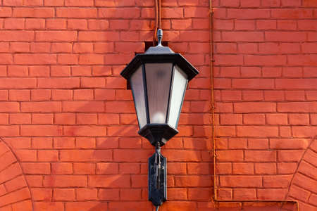 Forged lantern on a red brick wall with  space for lettering or design Reklamní fotografie