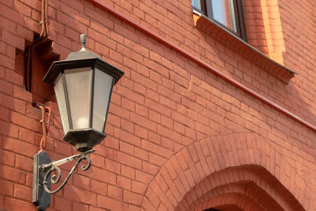 Forged lantern on a red brick wall