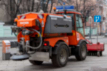 Defocused photo a sweeper cleans the sidewalk on the street. Close up. Blurred image.