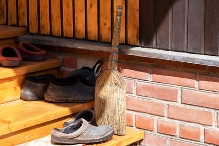 Broom and garden shoes on the threshold of a rural house in the rays of the bright sun