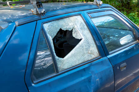 Fragment of car interior through blurred background of broken glass door as a result of crime