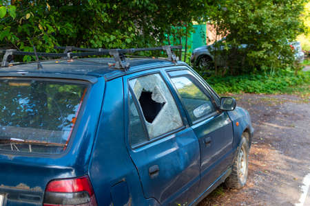 Car with broken rear door glass on the side of a country road. Consequence of crime, theft