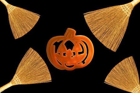 Brooms and pumpkin shape isolated on black background. Background to Halloween