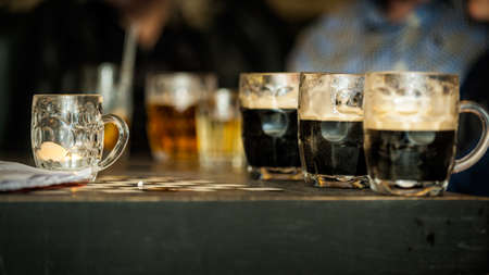 Horizontal colour image of half full beer glasses on the table of a bar Standard-Bild