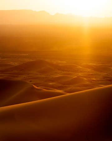 desert sunset: Vertical colour image of sunset and speeding car from sand dunes in Erg Chebbi, Morocco Stock Photo