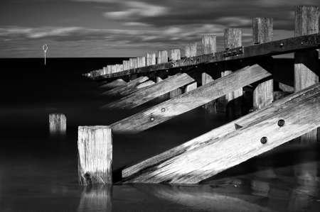 Horizontal black   white image of wooden wave breakers photo