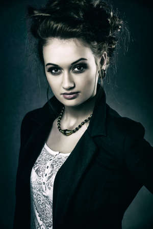 Horizontal color image  Studio shot of a young and attractive female model showing confidence wearing a white nett blouse and black jacket  Strong dark feel to post-processing   photo