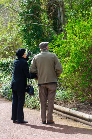 Vertical color image of a senior couple taking a walk in a park while holding hands on a sunny day photo