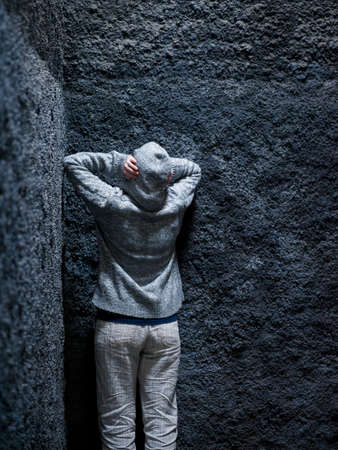 madhouse: Scared, insane woman hiding in a corner of an ancient building  Stock Photo
