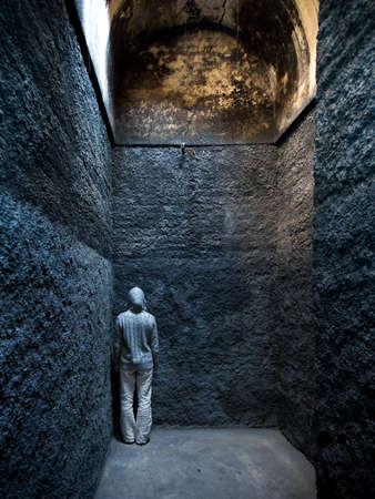 Scared, insane woman hiding in a corner of an ancient building  Standard-Bild