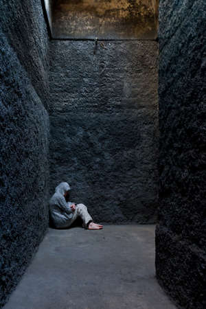 Scared, insane woman hiding in a corner of an ancient building  스톡 콘텐츠
