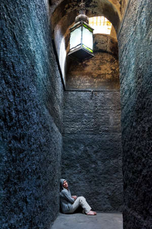 Scared, insane woman hiding in a corner of an ancient building  Stock Photo