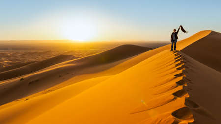 Traveler in the desert, active young woman trekking in hot sandy wilderness, dramatic sunset, summertime adventure, extreme tourism concept photo