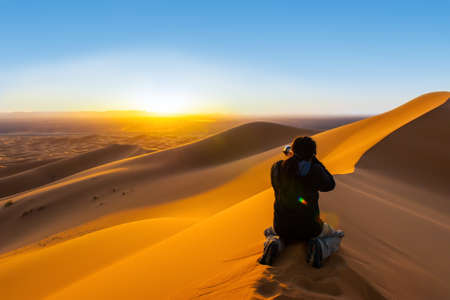 Handsome man with dreadlocks taking a photograph of sunset fron a sand dune
