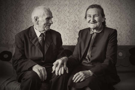 Cute 80 plus year old married couple posing for a portrait in their house. Love forever concept.  Stock Photo