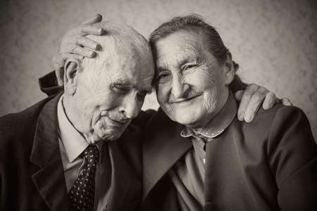 Cute 80 plus year old married couple posing for a portrait in their house  Love forever concept   Banco de Imagens