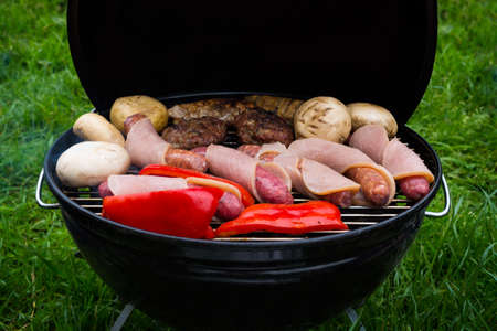 High angle view of succulent steaks,burgers, sausages and vegetables cooking on a barbecue over the hot coals on a green lawn outdoors photo