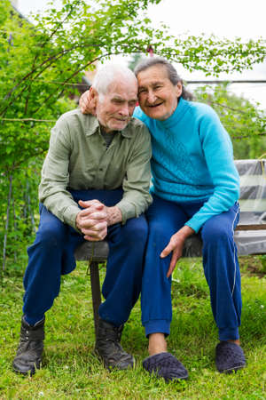 Cute 80 plus year old married couple posing for a portrait in their garden  Love forever concept   photo